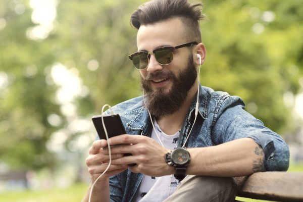 bearded young man on phone on park bench by LukaFunduk